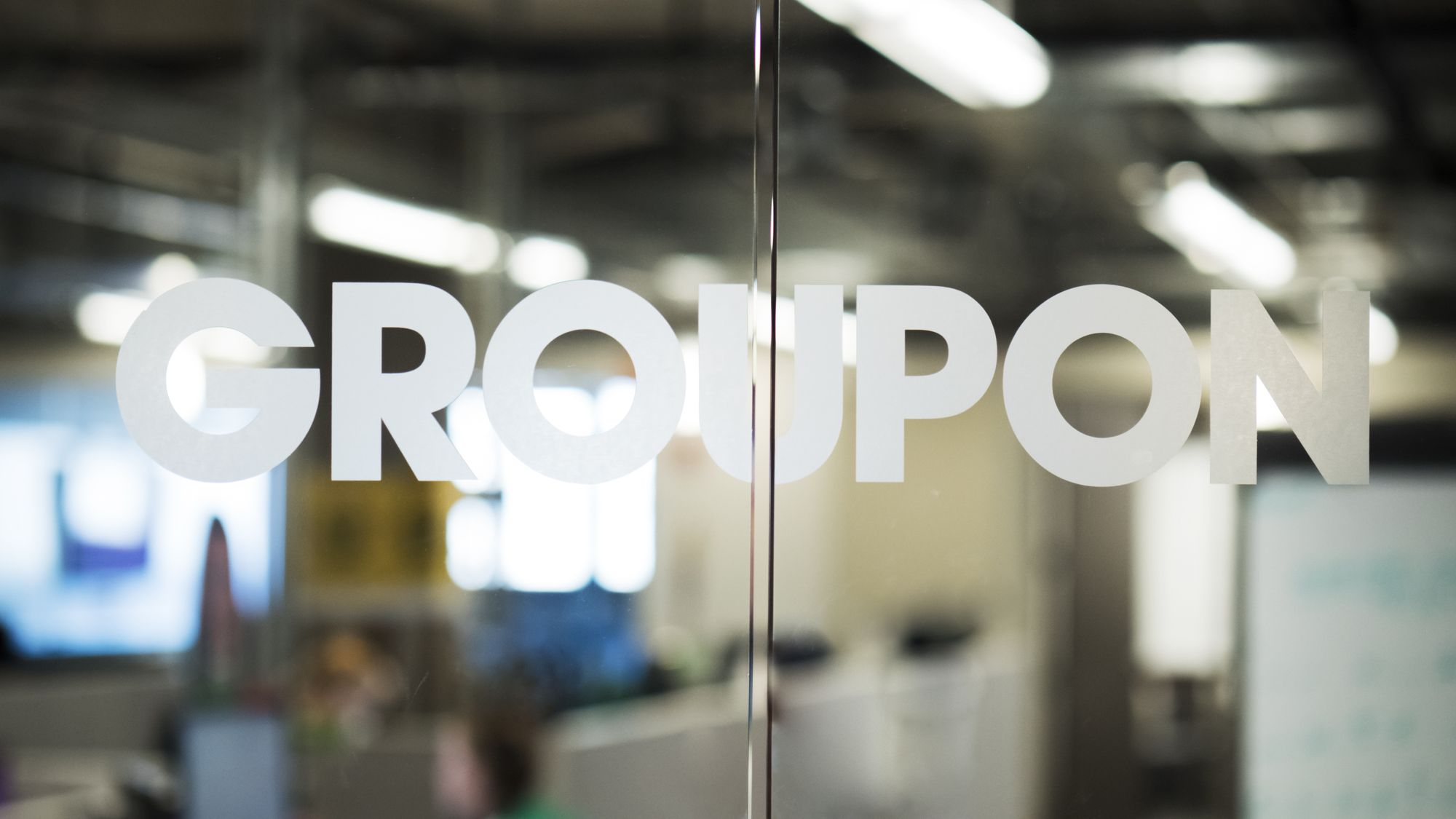 Glass doors with Groupon logo and blurred office in background